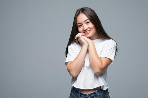 Donna asiatica che posa e che distoglie lo sguardo sopra il fondo grigio