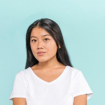 Donna asiatica che posa e che esamina macchina fotografica