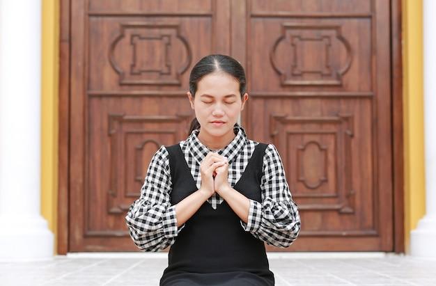 Donna asiatica che prega in chiesa