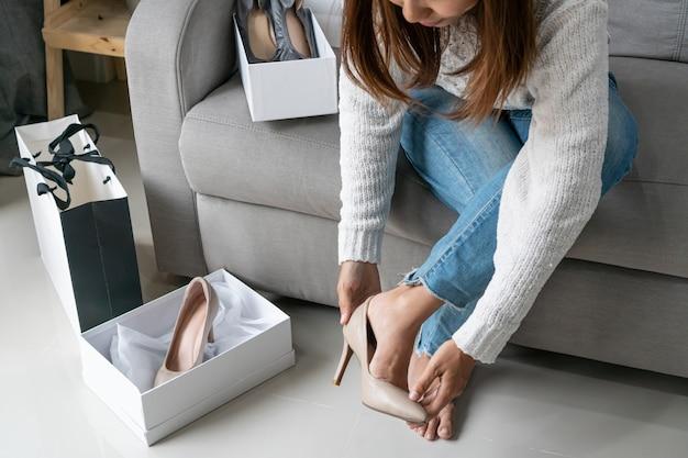 Donna asiatica che prova la sua nuova scarpa del tacco alto e che si siede sul sofà a casa, stile di vita digitale con tecnologia, concetto di commercio elettronico