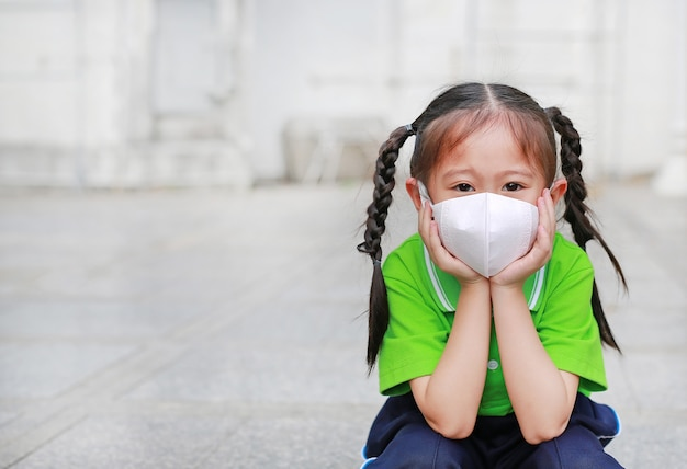 Donna asiatica che respira indossando una maschera protettiva contro l'inquinamento atmosferico nella città di bangkok