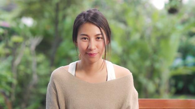 Donna asiatica che ritiene sorridere felice e che guarda mentre rilassi sulla tavola in giardino a casa di mattina. le donne di stile di vita si rilassano a casa concetto.
