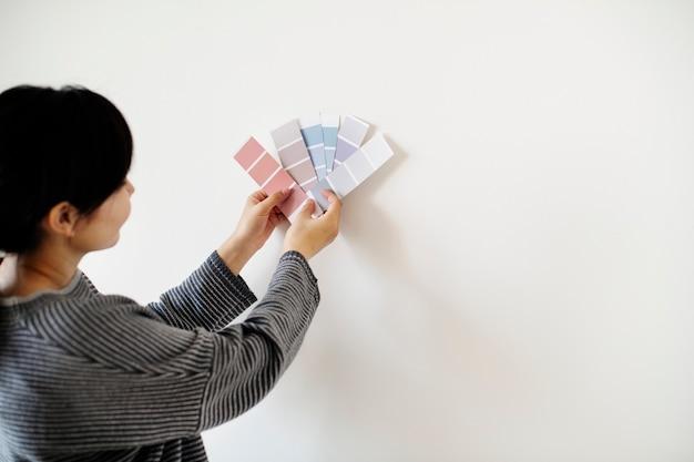 Donna asiatica che sceglie il colore della parete
