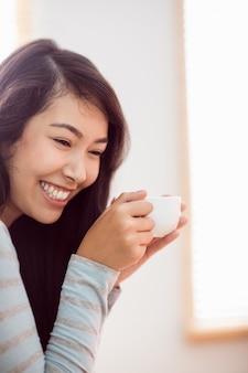 Donna asiatica che si distende sullo strato con caffè
