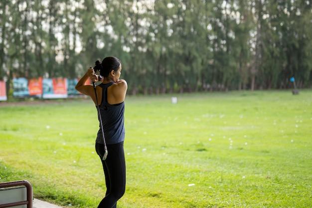 Donna asiatica che si esercita nella sua oscillazione al campo pratica di golf di srinakarin.