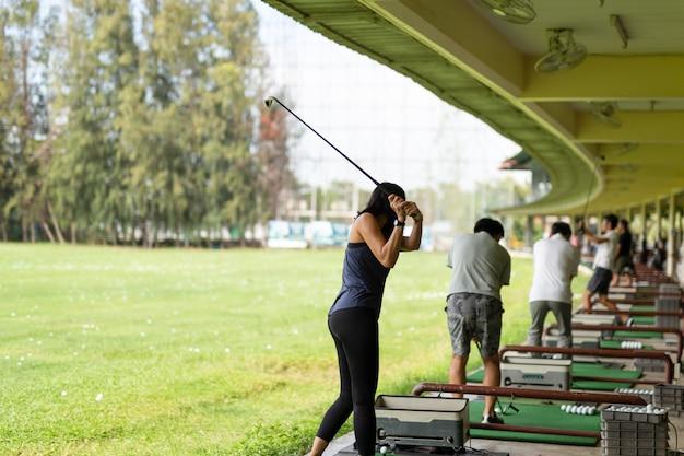 Donna asiatica che si esercita nella sua oscillazione di golf alla gamma di azionamento di golf.