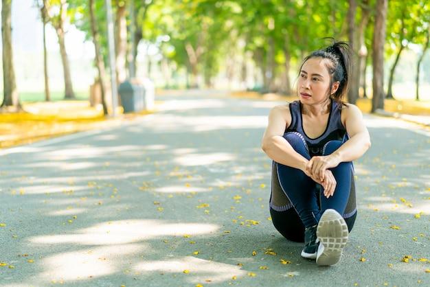Donna asiatica che si siede e si rilassa in abbigliamento sportivo dopo l'esercizio al parco