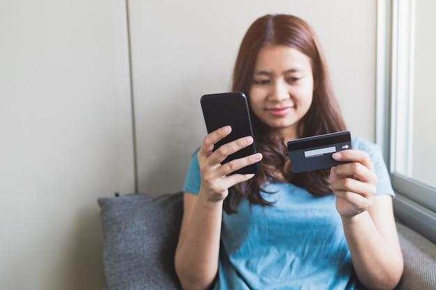 Donna asiatica che si siede su un divano grigio e lei sta usando una carta di credito per lo shopping online tramite telefono cellulare