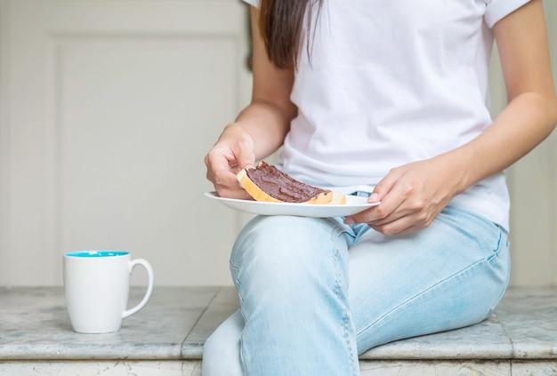 Donna asiatica che si siede sulla sedia di marmo davanti a casa per fare colazione al mattino