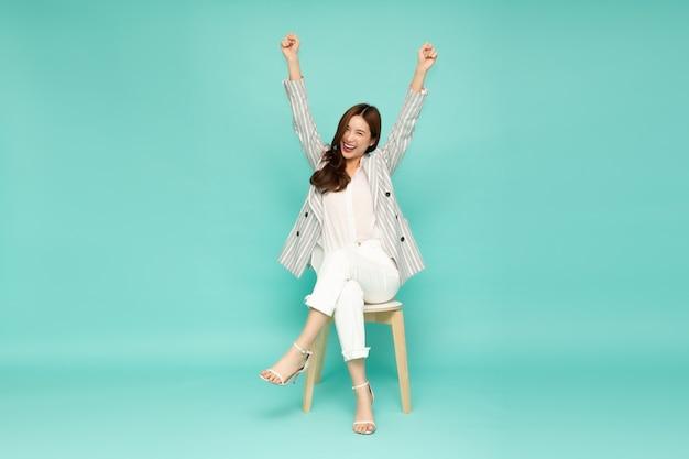 Donna asiatica che si siede sulla sedia moderna bianca