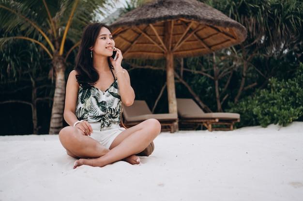 Donna asiatica che si siede sulla spiaggia e che per mezzo del telefono