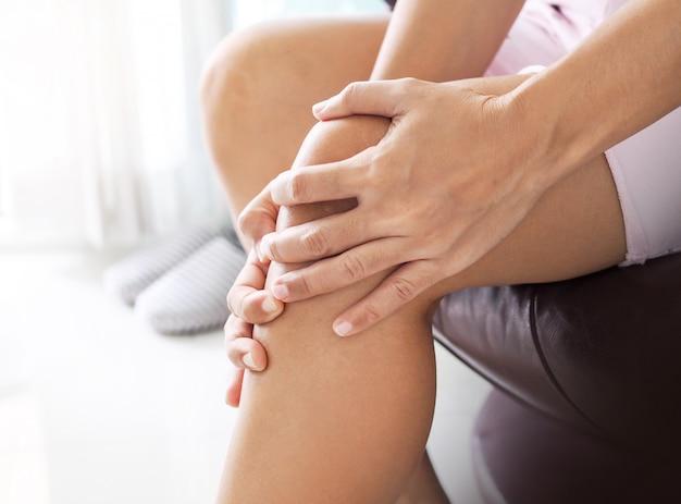 Donna asiatica che soffre di dolore alle gambe e al ginocchio.