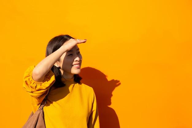 Donna asiatica che sorride nella parte superiore arancione con la mano sulla fronte che esamina macchina fotografica