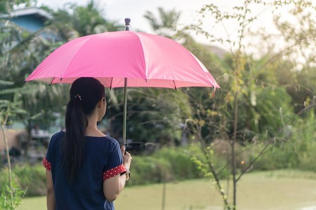 Donna asiatica che sta con l'ombrello rosa nel parco.