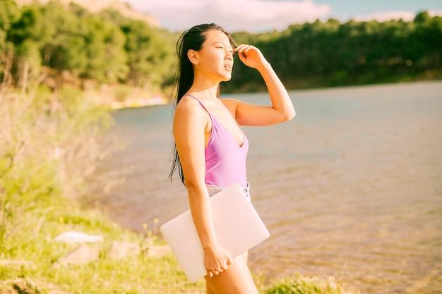 Donna asiatica che sta vicino al lago e che tiene computer portatile