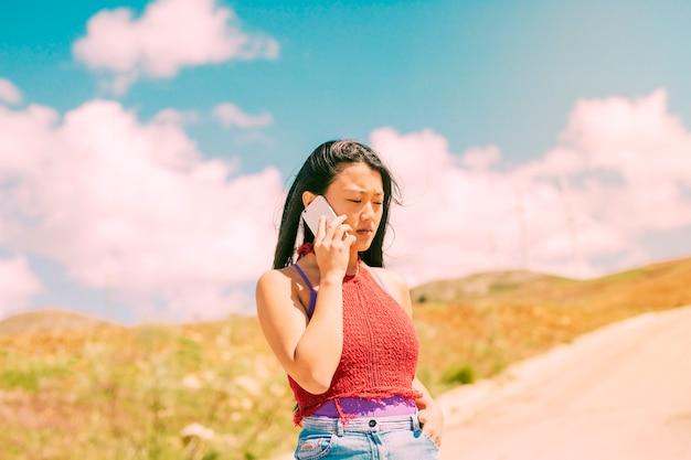 Donna asiatica che telefona che cammina nella campagna