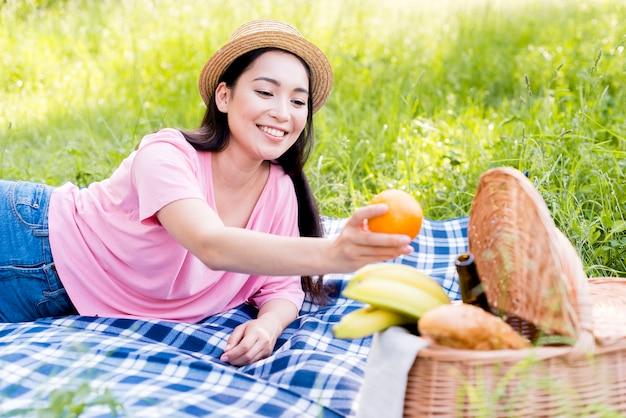 Donna asiatica che tiene arancio a disposizione