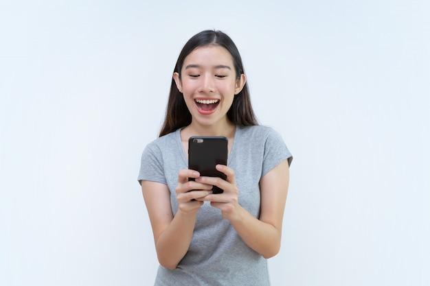 Donna asiatica che tiene smartphone, chiacchierando dal telefono cellulare, leggendo il messaggio di testo