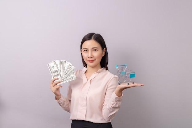 Donna asiatica che tiene soldi e carrello della spesa in mano