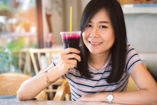 Donna asiatica che tiene un succo di barbabietola con felice, concetto nel cibo sano.