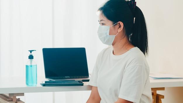Donna asiatica che usando la mano del lavaggio del disinfettante della mano del gel dell'alcool prima della compressa aperta per proteggere il coronavirus. le donne spingono l'alcool per pulire per l'igiene quando il distanziamento sociale rimane a casa e il tempo di auto-quarantena