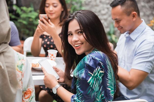 Donna asiatica che usando linguetta mentre con gli amici