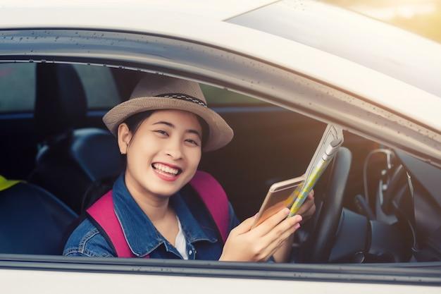 Donna asiatica che usando smartphone e mappa tra guida auto in viaggio su strada