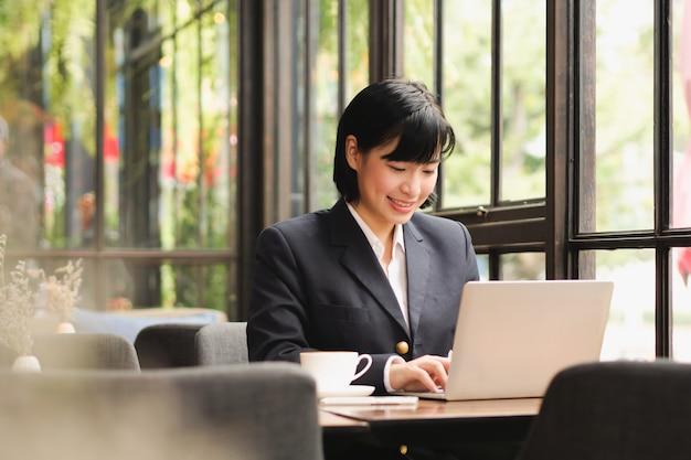Donna asiatica che utilizza computer portatile e che beve caffè nel caffè della caffetteria