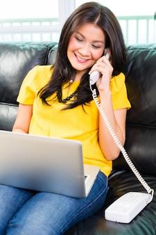 Donna asiatica che utilizza computer portatile e telefono sul divano