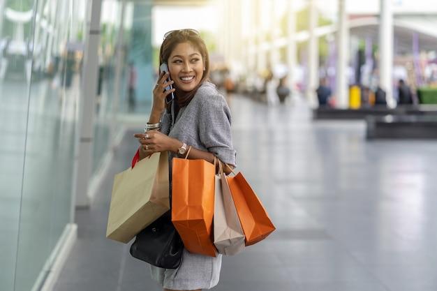 Donna asiatica che utilizza il telefono cellulare intelligente per parlare con un amico per comprare alcuni vestiti