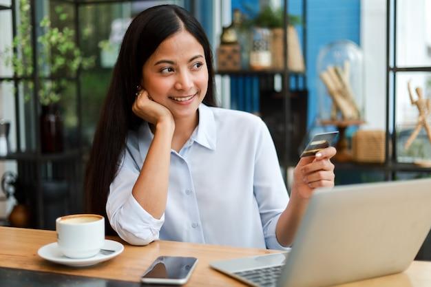 Donna asiatica che utilizza la carta di credito che compera online nel caffè della caffetteria