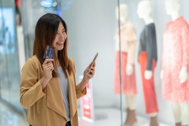 Donna asiatica che utilizza la carta di credito con il telefono cellulare per acquisto online nel grande magazzino