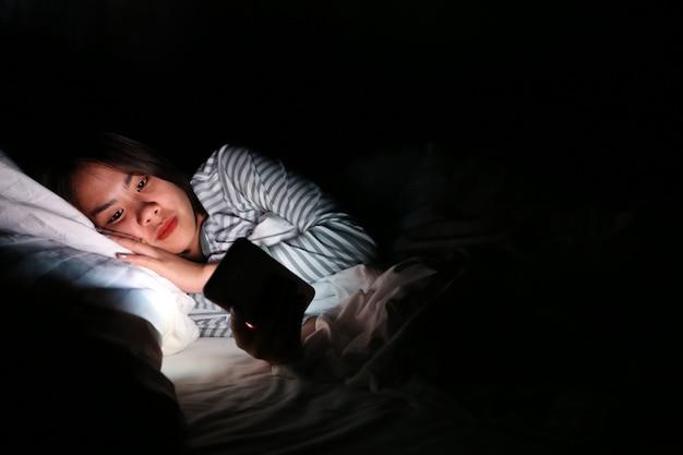 Donna asiatica che utilizza smartphone alla notte sul letto nella stanza scura