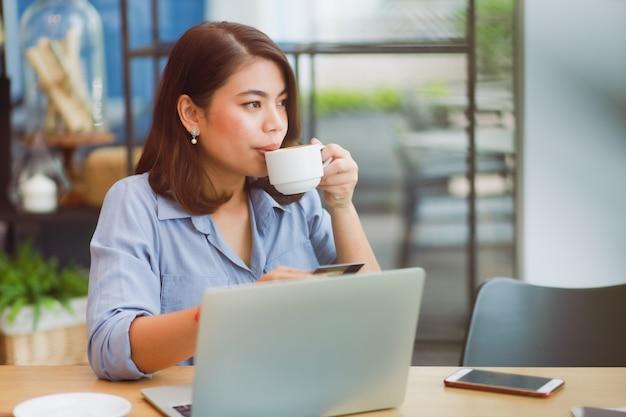 Donna asiatica che utilizza telefono cellulare con la carta di credito e il computer portatile per il pagamento online di compera nel caffè della caffetteria con gli amici