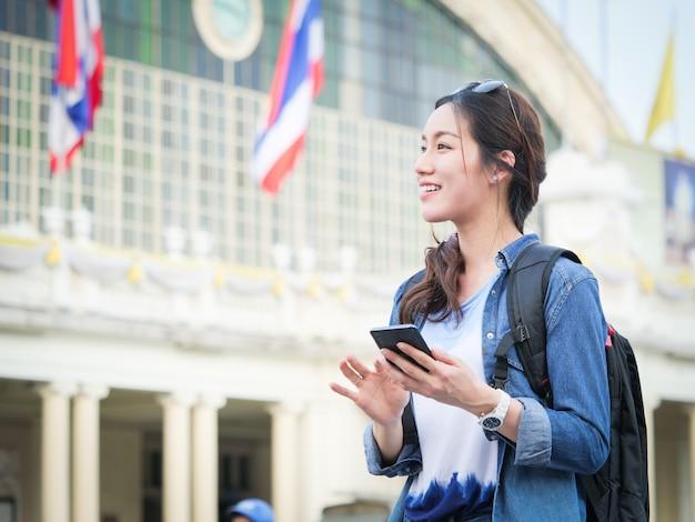 Donna asiatica che viaggia con il cellulare