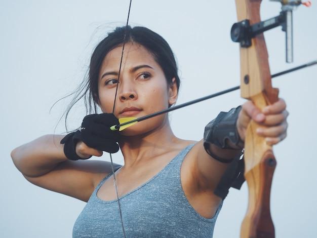 Donna asiatica con arco tiro con l'arco