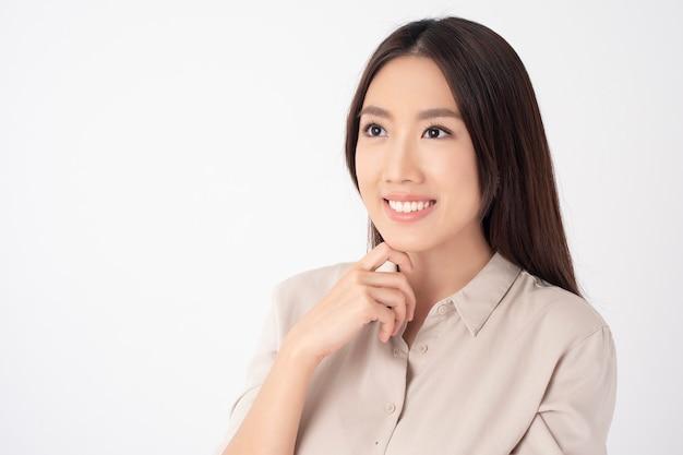 Donna asiatica con bei denti sulla parete bianca