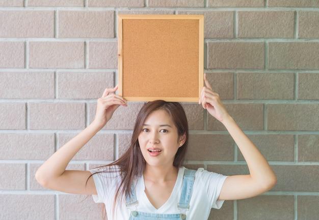 Donna asiatica con bordo di sughero in mano con la faccia eccitata