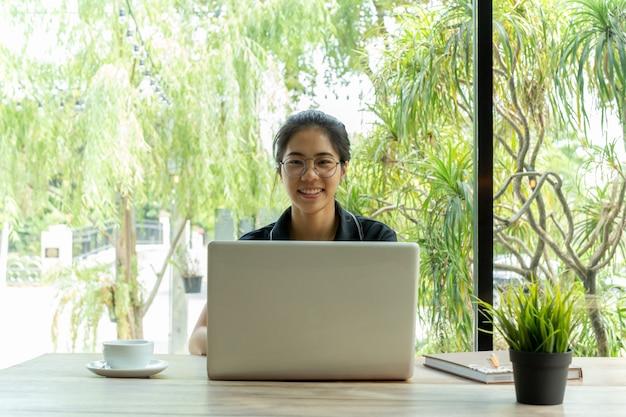Donna asiatica con gli occhiali che sorride per mezzo del computer portatile con la tazza di caffè sulla tabella.
