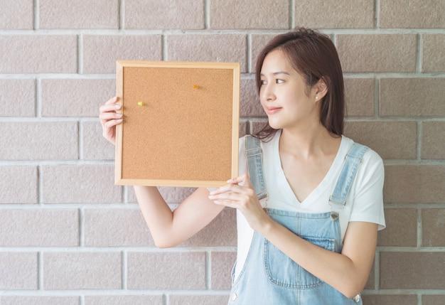 Donna asiatica con il bordo del sughero a disposizione con il fronte sorridente