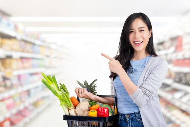 Donna asiatica con il cestino della spesa pieno delle drogherie in supermercato