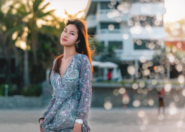 Donna asiatica con il ritratto bianco della pelle di bellezza su una spiaggia