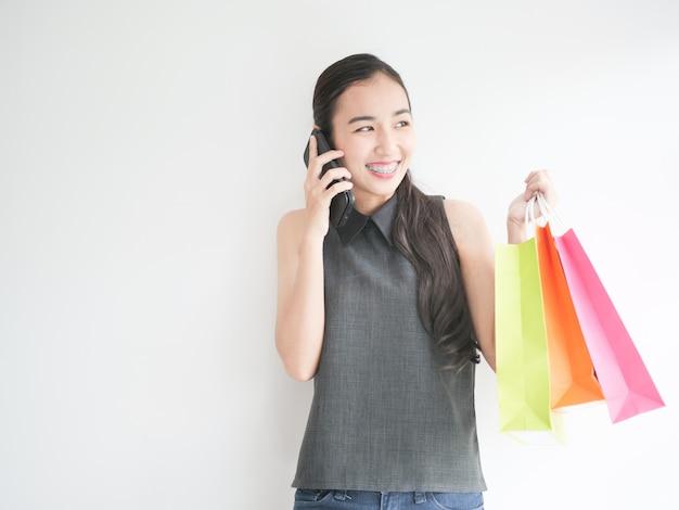 Donna asiatica con il sacchetto della spesa nel salotto