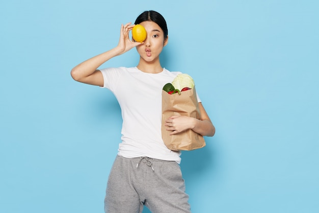 Donna asiatica con la borsa delle verdure, concetto di dieta