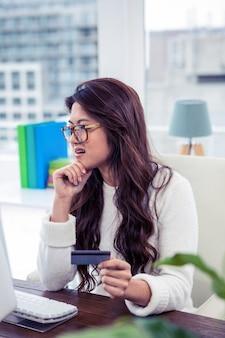 Donna asiatica con la mano sulla carta di credito della tenuta del mento in ufficio