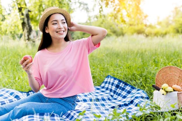 Donna asiatica con la mela che si siede sulla coperta