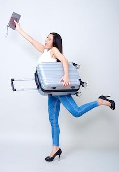 Donna asiatica con la valigia luminosa