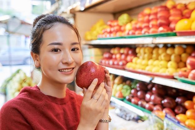 Donna asiatica con mela rossa