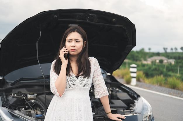 Donna asiatica con un'automobile rotta che per mezzo del telefono cellulare per chiamare assistenza sul bordo della strada.