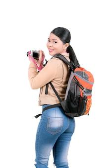 Donna asiatica con uno zaino che tiene una macchina fotografica per scattare foto